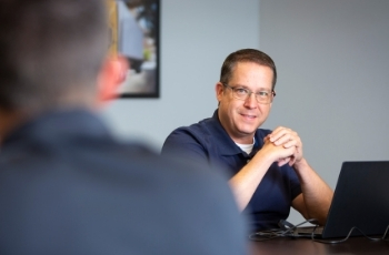 An in-house semi truck financing rep for TLG Financial smiles at a client over a conference room table.