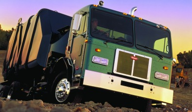 A purple refuse truck offered by TLG Peterbilt.
