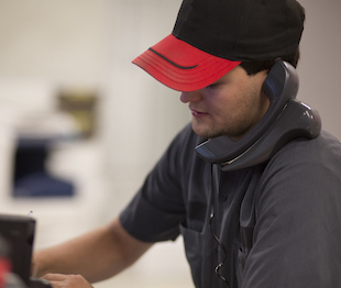 A TLG Peterbilt semi truck road service technician makes a phone call.