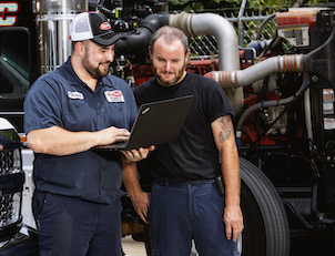 Two semi truck service repair technicians conduct mobile service for a TLG Peterbilt customer.