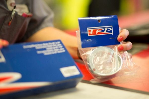 A TLG parts representative holds up a part available on special.