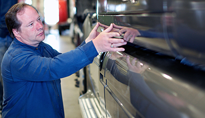 A TLG Peterbilt semi truck service repair technician determines a truck's repair needs.