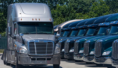 A lineup of Peterbilt, Kenworth and Freightliner used trucks.