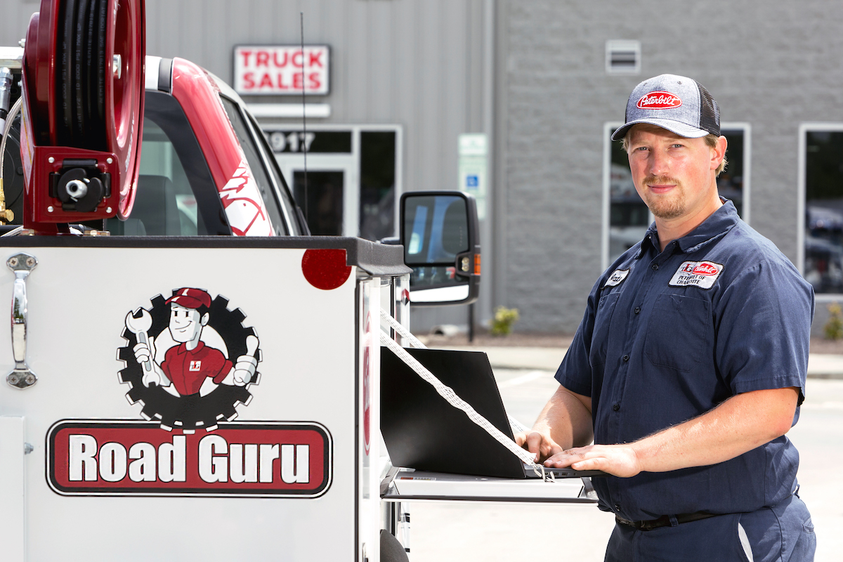 A TLG team member stands next to a Road Guru truck.