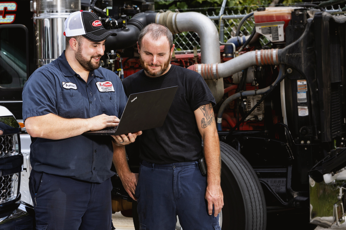 Two TLG team members smile as they perform mobile service on a truck engine.